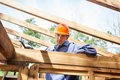 Confident construction worker hammering nail on portrait of male timber frame at site Royalty Free Stock Image