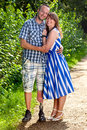 Confident couple in a loving embrace attractive smiling young standing outdoors on gravel path the men is handicapped amputee Royalty Free Stock Photos