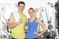 Confident couple with towel and water bottle in gym portrait of young Royalty Free Stock Photo