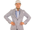 Confident determined architect or engineer wearing a hardhat and jacket standing staring straight ahead with his hands on his hips Royalty Free Stock Image