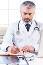 Confident doctor at work mature grey hair writing something in note pad while sitting his working place Stock Image