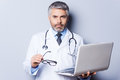 Confident and experienced doctor mature working holding laptop looking at camera while standing against grey background Stock Images