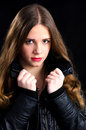 Confident fashionable teenager pretty young girl in black jacket isolated on black background Stock Images
