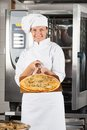 Confident female chef presenting pizza portrait of at commercial kitchen Stock Photo