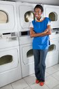 Confident female helper standing by dryers full length portrait of young african american in laundry Royalty Free Stock Photos