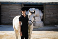 Confident female jockey standing by white horse at barn Royalty Free Stock Photo