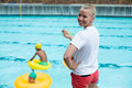 Confident female lifeguard holding whistle at poolside Royalty Free Stock Photo