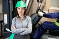 Confident female supervisor with forklift driver portrait of men driving in warehouse Royalty Free Stock Image