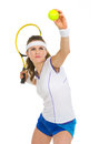 Confident female tennis player serving ball isolated on white Stock Photography
