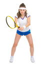 Confident female tennis player in stance on white Stock Photography