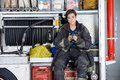 Confident firewoman holding coffee mug in truck portrait of while sitting at fire station Stock Image