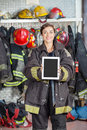 Confident firewoman showing digital tablet with portrait of blank screen at fire station Royalty Free Stock Image