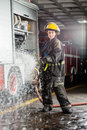 Confident firewoman spraying water during practice portrait of young at fire station Royalty Free Stock Images