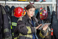 Confident firewoman using digital tablet at fire portrait of in uniform station Royalty Free Stock Photography