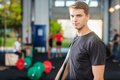 Confident fit man holding barbell bar portrait of at gym Stock Images