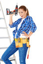 Confident happy diy handy woman standing on a stepladder with a tool belt round her waist brandishing an electric drill in the air Royalty Free Stock Photo