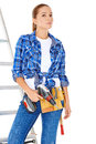 Confident happy diy handy woman standing on a stepladder with a tool belt round her waist brandishing an electric drill in the air Royalty Free Stock Photography