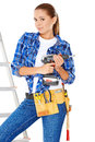 Confident happy diy handy woman standing on a stepladder with a tool belt round her waist brandishing an electric drill in the air Royalty Free Stock Images