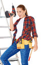 Confident happy diy handy woman standing on a stepladder with a tool belt round her waist brandishing an electric drill in the air Stock Images
