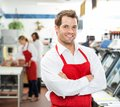 Confident male butcher standing arms crossed at portrait of store with colleagues working in background Stock Photos