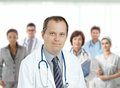 Confident male doctor in front of medical team middle aged looking at camera smiling background Royalty Free Stock Photos