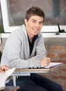 Confident man sitting at desk in classroom portrait of young Stock Photos