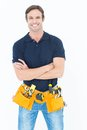 Confident man with tool belt around waist over white background Royalty Free Stock Photo