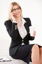 Confident mature businesswoman beautiful talking on the mobile phone and holding a coffee cup Stock Photo