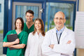 Confident mature male doctor with team in background portrait of at clinic Royalty Free Stock Photo