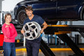 Confident mechanic holding hubcap with customer portrait of while standing female at garage Royalty Free Stock Photos