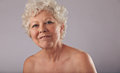 Confident old woman with smile on her face portrait of beautiful naked senior looking happy against grey background caucasian Stock Image