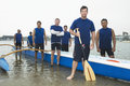 Confident outrigger canoeing team group portrait of multiethnic on beach Royalty Free Stock Photo