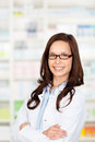 Confident pharmacist portrait of a female standing in drugstore Stock Image