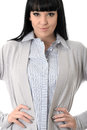 Confident pleased assertive composed woman with hands on hips young long straight black hair and hispanic or european features Stock Photography