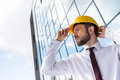 Confident professional architect in hard hat against building Royalty Free Stock Photo
