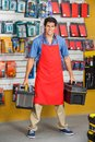 Confident salesman holding toolboxes in store full length portrait of young hardware Royalty Free Stock Images