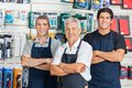 Confident salesmen in hardware store portrait of happy standing arms crossed Royalty Free Stock Photo