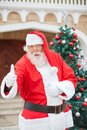 Confident santa claus gesturing thumbsup portrait of against christmas tree Royalty Free Stock Photography