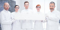 Confident scientists in lab close up of five a chemistry holding hands an empty banner and looking the camera with a Royalty Free Stock Images