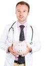 Confident, serious male doctor, nurse holding piggy bank Royalty Free Stock Photo