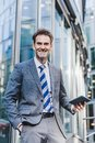 Businessman stands in front of an office building with a tablet Royalty Free Stock Photo