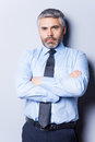 Confident and successful mature man in shirt tie looking at camera keeping arms crossed while standing against grey background Royalty Free Stock Photos