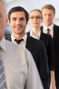 Confident and successful young men in formalwear looking at camera smiling while standing in line with another people Royalty Free Stock Image