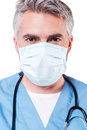 Confident surgeon mature grey hair doctor in surgical mask looking at camera while standing isolated on white Stock Photos