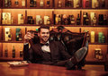 Confident upper class man with glass of beverage in gentlemen`s club Royalty Free Stock Photo