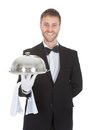 Confident waiter holding domed tray Royalty Free Stock Photo