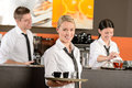Confident waitress serving coffee with tray colleagues working behind Stock Photography