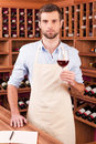 Confident winery owner young man in apron holding glass with red wine while standing in wine cellar Royalty Free Stock Photography
