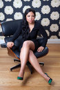 Confident woman sitting on a leather chair Royalty Free Stock Images