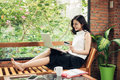 Confident young asian woman in smart casual wear using laptop. Royalty Free Stock Photo